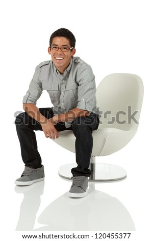 College age man sitting on a modern white chair isolated on white - stock photo