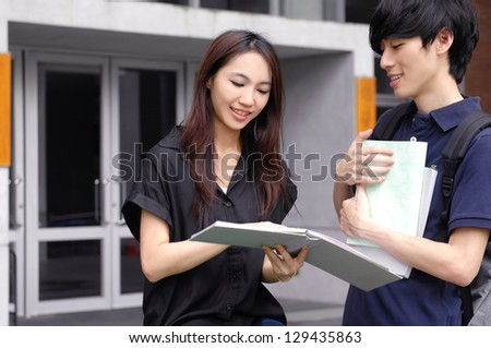 college couple student olding laptop on campus - stock photo