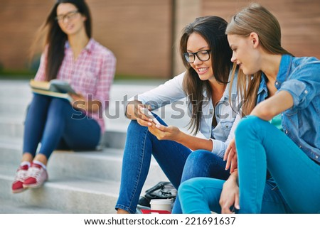 College friends watching pics on phone at break - stock photo