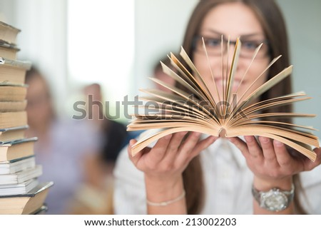 College girl student on university campus with open book in hands - stock photo