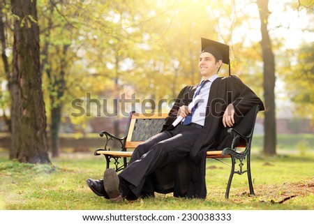 College graduate enjoying in park seated on a bench - stock photo