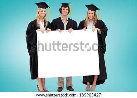 College graduates showing card against blue vignette - stock photo