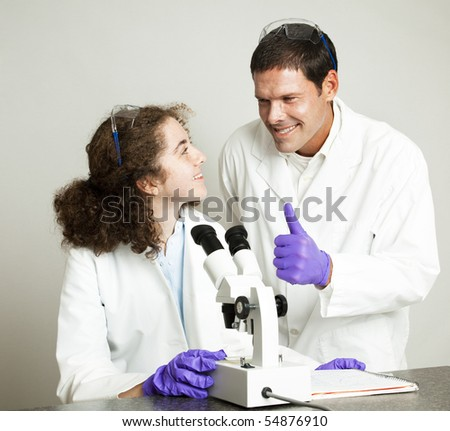 College (or high school) student gets a thumbs up from her science professor. - stock photo