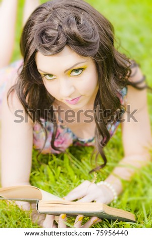 College Or University Student Reading A Book In A Field Tests Her Memory Skills By Looking Up To Remember Recall And Recollect What She Just Studied - stock photo