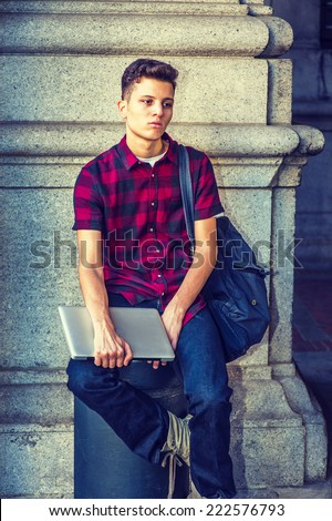 College Student. Dressing in short sleeve, black, red patterned shirt, jeans, carrying shoulder bag, holding laptop computer, a young guy is sitting on metal pillar on street, sad, relaxing, thinking. - stock photo