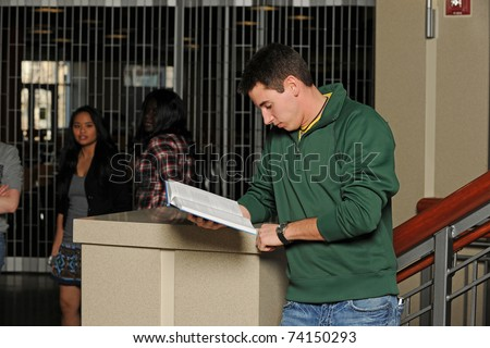 College student holding a book with diversity group in the background - stock photo
