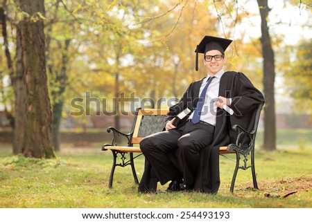College student holding diploma and a book seated on bench in park  - stock photo