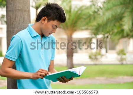 College student reading book near the university - stock photo