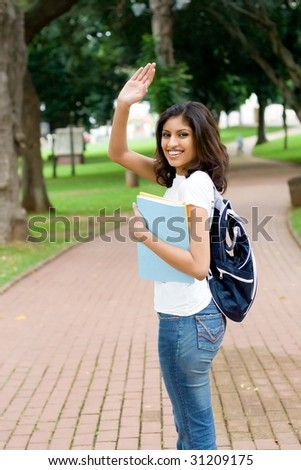 college student saying good bye and waving to her friend - stock photo