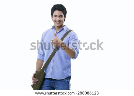 College student showing thumbs up sign over white background - stock photo