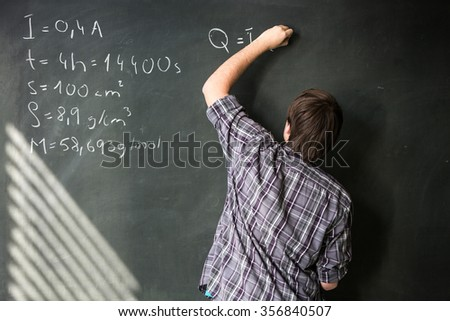 College student solving a math problem during math class in front of the blackboard/chalkboard (color toned image) - stock photo