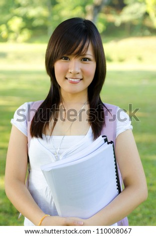 College student standing outside campus, green park - stock photo