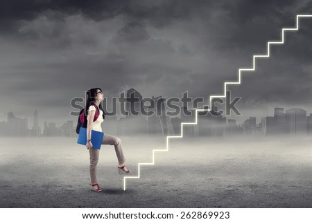 College student stepping up on stairs to gain her success - stock photo