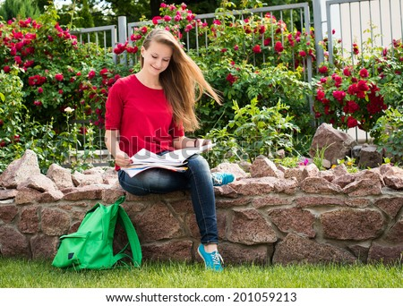 College student studying at campus near rose bushes. Preparing fo exams outdoors. - stock photo