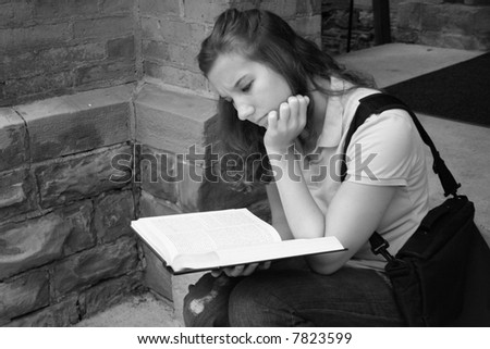 College student studying on the steps of a college building - stock photo