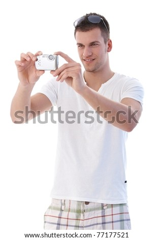 College student taking photo by digital camera, smiling.? - stock photo