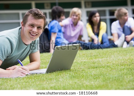 College students sitting and talking on campus lawn - stock photo