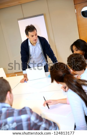 College teacher in class with group of students - stock photo