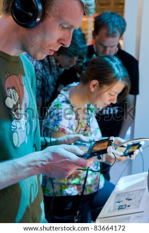 COLOGNE - AUGUST 20: Videogamers playing with Nintendo 3ds at GamesCom 2011, the most important European video games Expo August 20, 2011 in Cologne, DE - stock photo