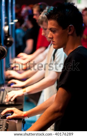 COLOGNE - AUGUST 22: Young video gamers play an online game during GamesCom 2009 August 22, 2009 in Cologne, Germany. - stock photo
