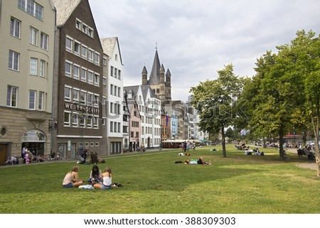 Cologne, Germany - August 27, 2013: People sitting on the grass at the riverfront in Cologne on August 27, 2013 in Cologne, Germany - stock photo