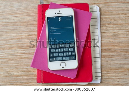 Cologne, Germany- February 21, 2016: Iphone 5 White with opened Tumbler application in german language on the table. - stock photo
