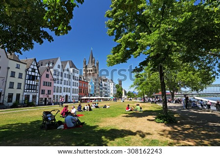COLOGNE, Germany - May 29: Buildings along an embankment and the High Cathedral of St. Martin near Hohenzollern Bridge on May 29,2011 in Cologne, Germany. Leisure and pleasure of travelers on vacation - stock photo