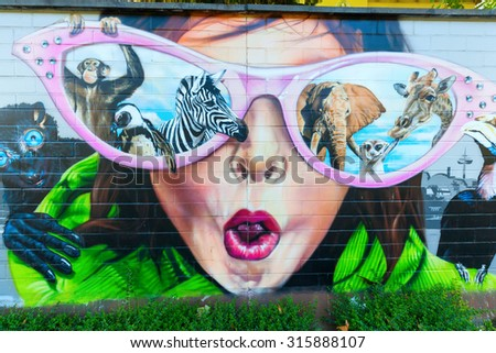 COLOGNE; GERMANY - SEPTEMBER 11, 2015: graffiti at the wall of the zoo of Cologne. As a result of a contest the winning artists painted parts of the wall in the year 2011. - stock photo