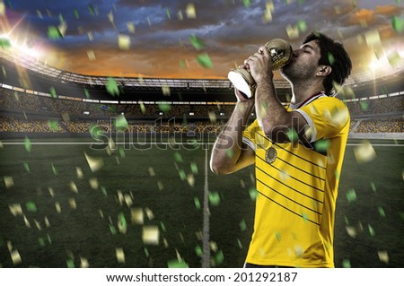 Colombian soccer player, celebrating the championship with a trophy in his hand. On a stadium. - stock photo
