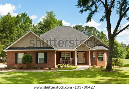 Colonial brick house with beautifully landscaped front yard and mature oak trees - stock photo