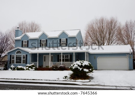 Colonial House Covered in Snow during Snowfall - stock photo