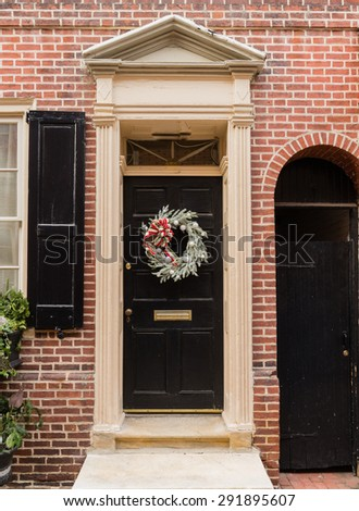 Colonial red doorway in historic Elfreth's Alley in Philadelphia with pediment and  christmas wreath - stock photo