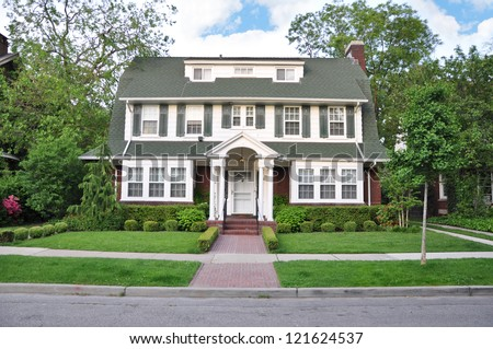 Colonial Style Home in Suburban Residential Neighborhood with Beautifully Landscaped front yard lawn - stock photo