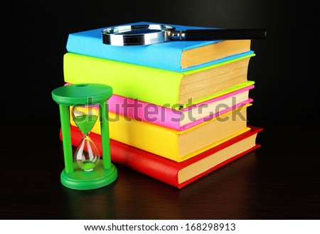color books with magnifying glass on table on black background - stock photo