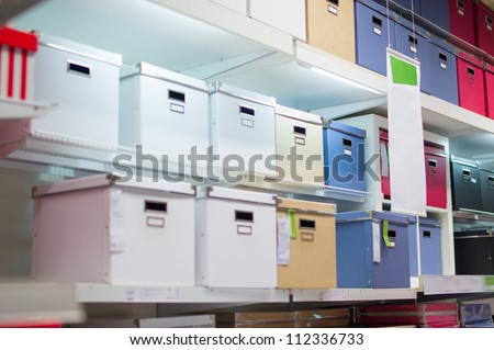 Color boxes for documents and goods on shelves in supermarket - stock photo