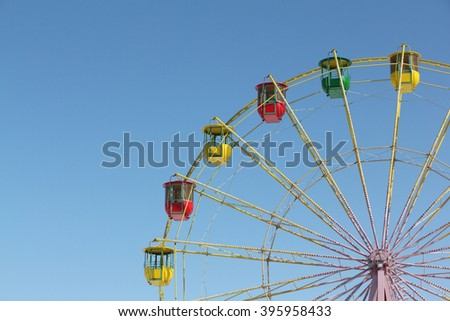 Color cabins of a ferris wheel against the blue sky - stock photo