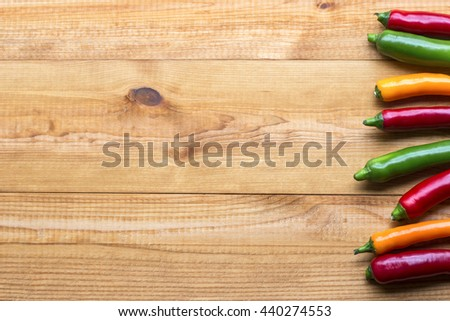 Color cayenne chilli peppers on wooden table. Image with copyspace. - stock photo
