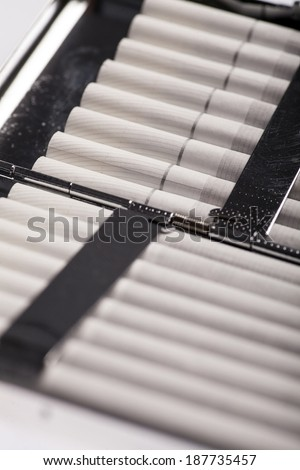 Color detail of a cigarette case with white cigarettes. - stock photo