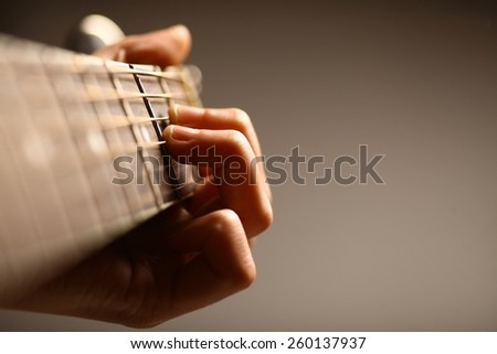Color detail of hands playing of an old, acoustic guitar. - stock photo