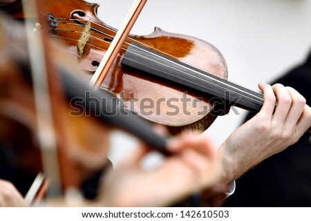 Color detail with the hands of a person playing the violin - stock photo