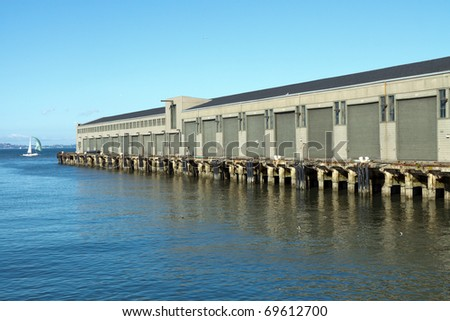Color DSLR image of dock and warehouse on a commercial pier, on water of San Francisco bay, California. Horizontal with copy space for text - stock photo