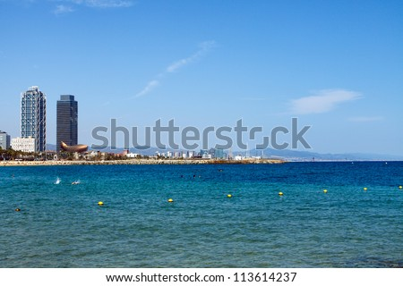Color DSLR landscape picutre of skyscrapers on the Mediterranean Sea in Barcelona, Spain.  The buildings are in the distance, framing the water.  In horizontal orientation with copy space for text - stock photo