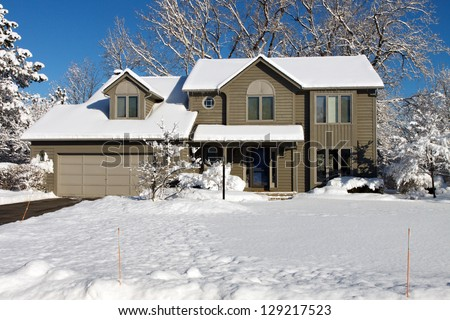 Color DSLR picture of a suburban colonial house covered in white winter snow.  The image of the home is in horizontal orientation with ample copy space for text. - stock photo