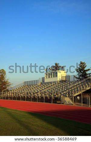 Color DSLR picture of American sports football stands at sunset. Bleachers are empty but crowds gather for high school sports games. Vertical with copy space for text. - stock photo