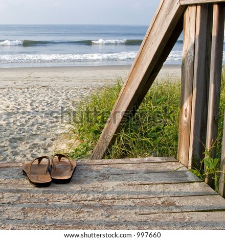 Color DSLR picture of leather sandals on boardwalk steps leading to the Atlantic Ocean.  The thong shoes are brown, the dune grass green and the water blue  Black and white version in my portfolio - stock photo