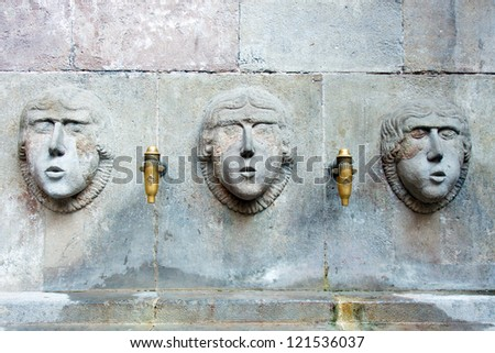 Color DSLR picture of three faces carved in the granite, forming a water drinking fountain Barcelona, Spain.  The unique image is in horizontal orientation with ample copy space for text. - stock photo