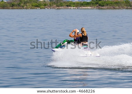 Color DSLR picture of two people, a man and a woman, speeding across the still salt water on a jet-ski trailing a foamy wake.  Water is calm.  From behind.  Horizontal with copy space for text. - stock photo