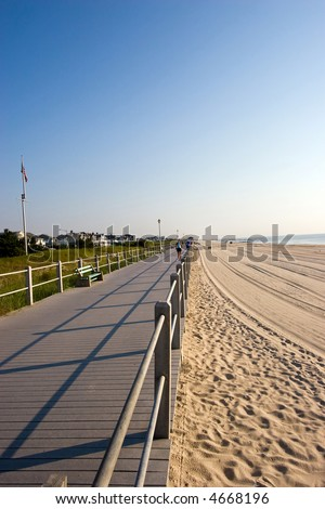 Color DSLR picture of wooden boardwalk along the beach on New Jersey shore.  Sand and surf on the right and grass covered sand dunes on left. Clear blue morning sky. Vertical with copy space for text - stock photo