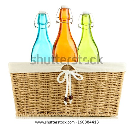 Color glass bottles in wicker basket, isolated on white - stock photo