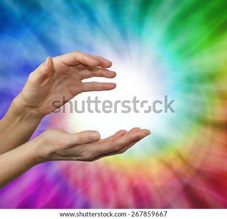 Color healing therapist sensing color energies - Female hands cupped in energy sensing position with a rainbow vortex behind and a ball of white energy in the center - stock photo